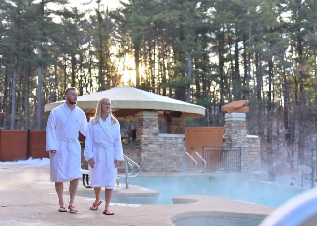 Man and woman walking along outdoor pool at Sundara